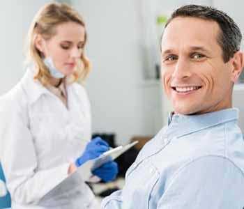A man is sitting on the dentist chair & Dentist near him
